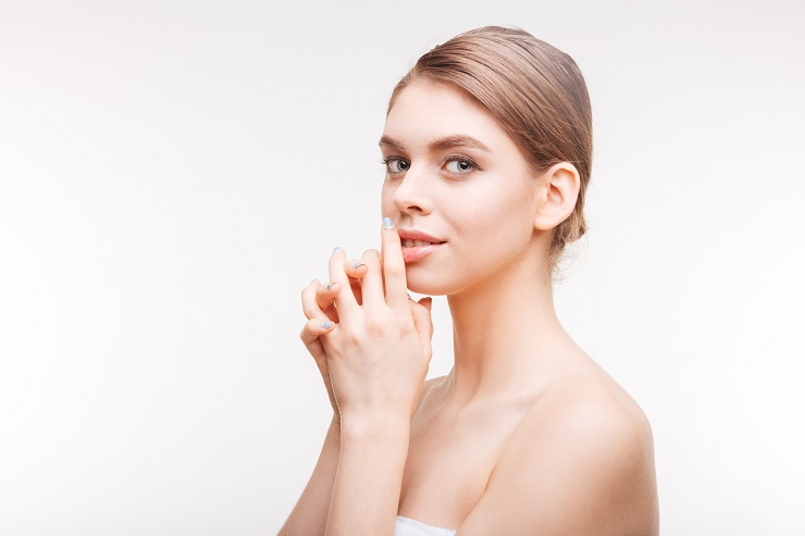 Beauty portrait of a young attractive woman with fresh skin looking at camera isolated on a white background
