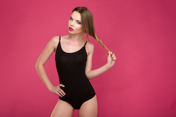 Fashion portrait of glamourous beautiful seductive model in black leotard playing with hair