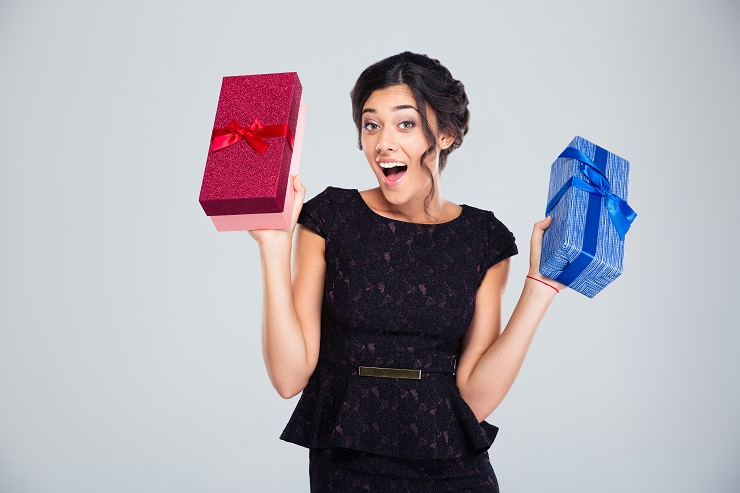 Laughing woman in black dress holding two gift boxes on gray background. Looking at camera
