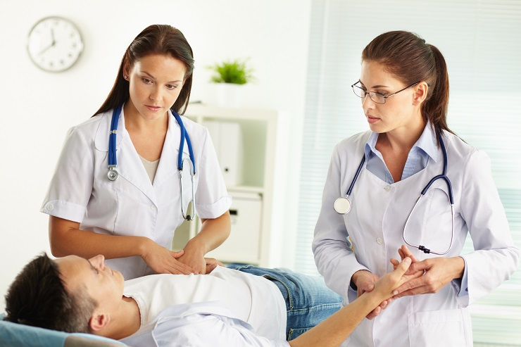 Female practitioners examining the patient looking for the source of pain