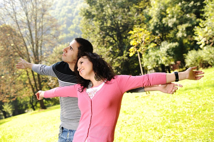 Two young relaxed people in nature with opened arms looking up and breathing fresh air