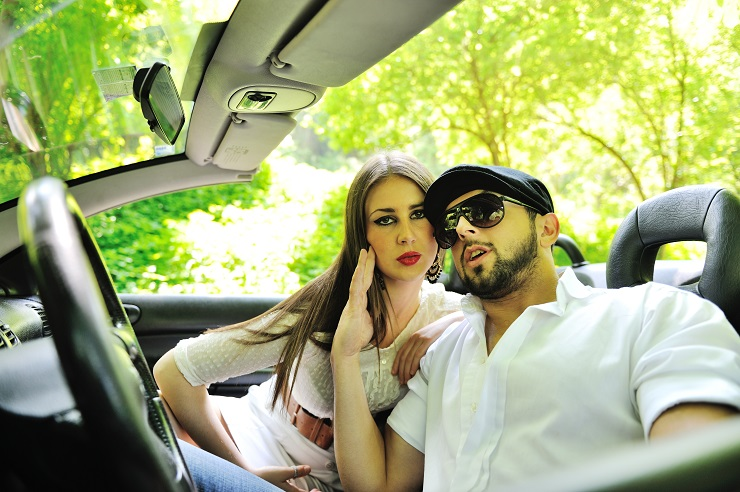 Young couple hanging together in car outdoors