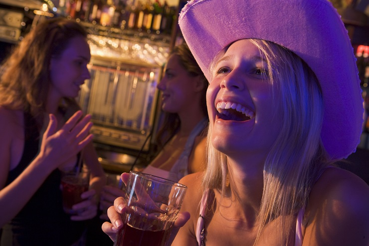 Young woman in cowboy hat laughing at a nightclub
