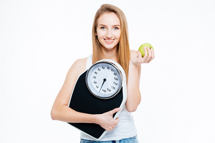 Portrait of lovely smiling young woman with fresh apple and scales over white background