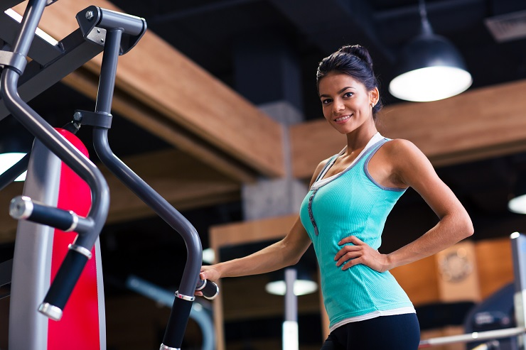 Portrait of a happy cute woman standing in fitness gym