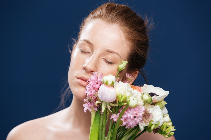 Beauty portrait of relaxed woman holding flowers over blue background