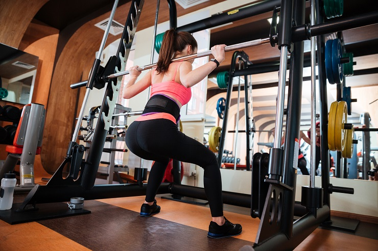 Back view of attractive young sportswoman doing squats with barbell in gym
