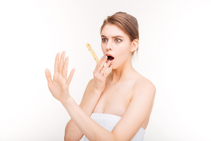 Beauty portrait of shocked young woman with emery board looking at her nails over white background