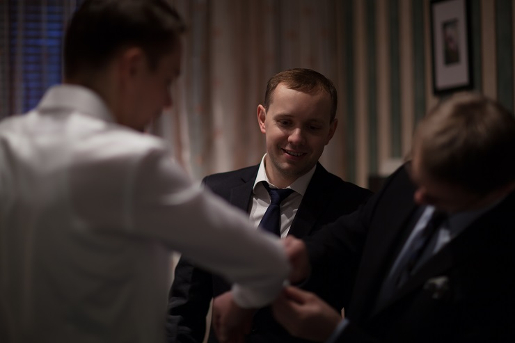 Two friends helping a groom to get ready for wedding ceremony by fixing cuff links