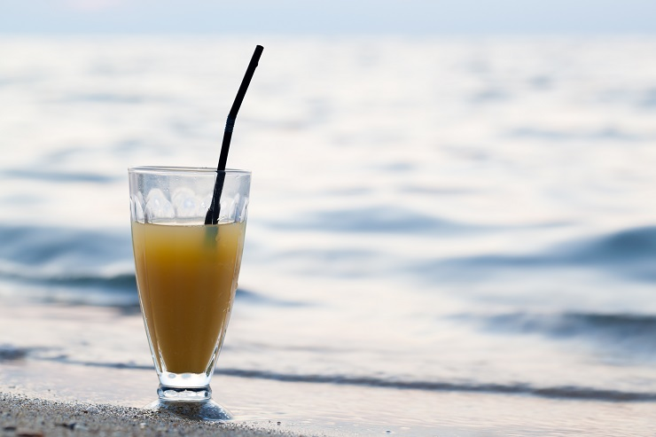 Close-up shot of glass of cocktail or fruit juice with straw standing on beach close to sea. Summer vacation