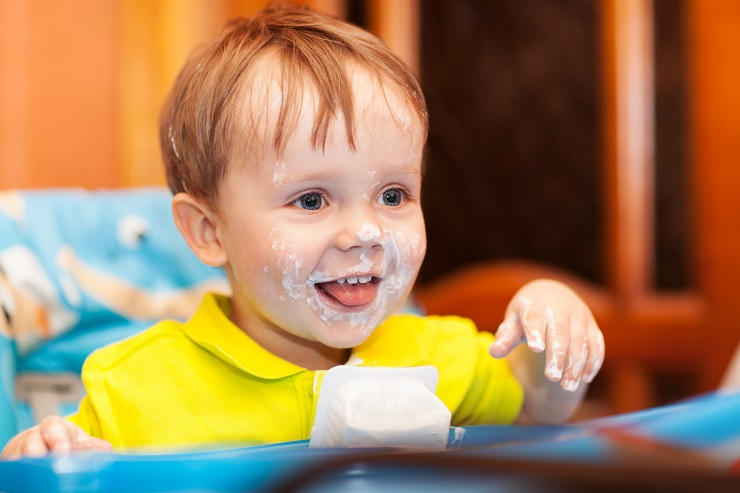 Close-up of shot of a happy cute boy sitting at feeding table, his face and hands dirty with cream yoghurt