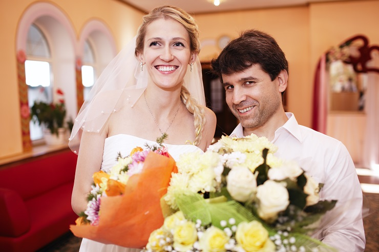 Smiling radiant beautiful bride and groom posing indoors with bouquets of flowers from well wishers at their wedding ceremony