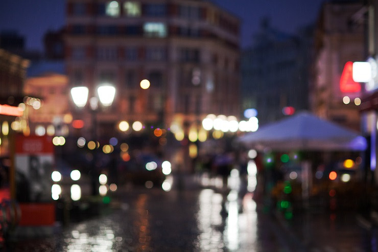 Blurred shot of rainy evening in the city. Street and lanterns lights reflecting on wet road