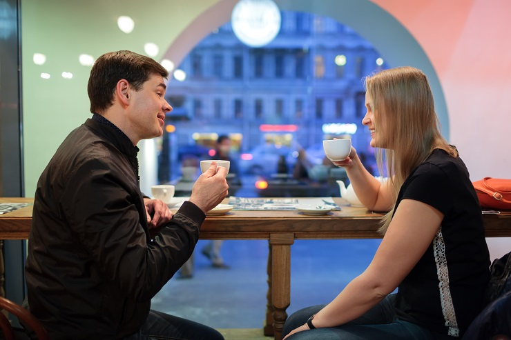 Man and woman chatting over a cup of coffee inside a cafe or restaurant