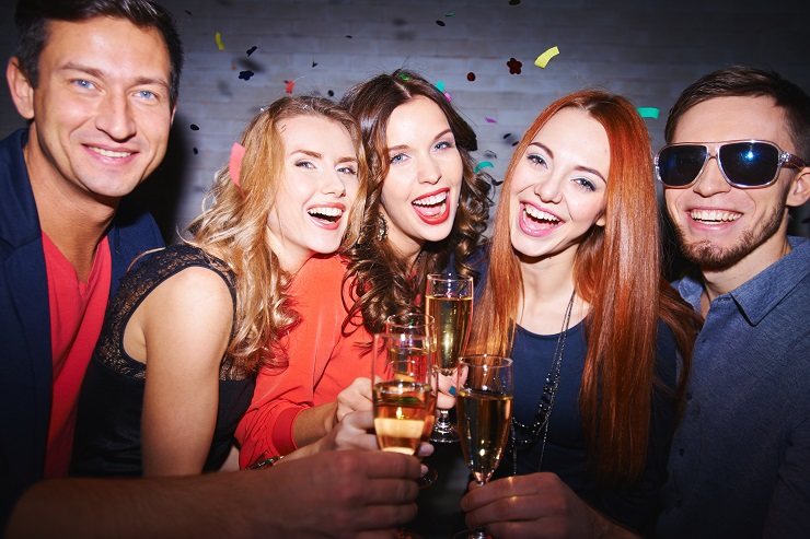 Ecstatic friends with champagne having party