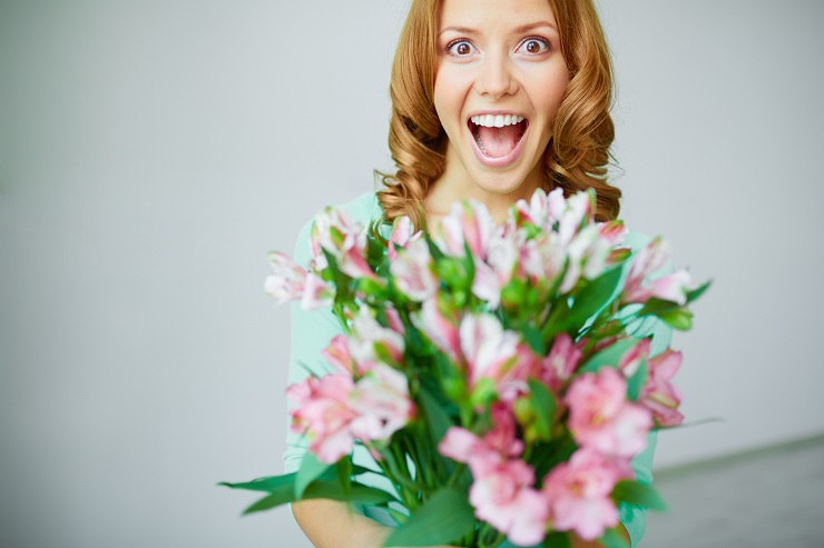 Portrait of ecstatic woman with bunch of flowers looking at camera