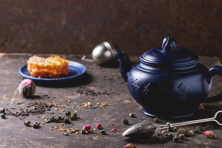 Blue ceramic teapot and plate with honeycombs, served with spoons, black and green tea lives over dark background. Chinese inscription on teapot - traditional tea drinking