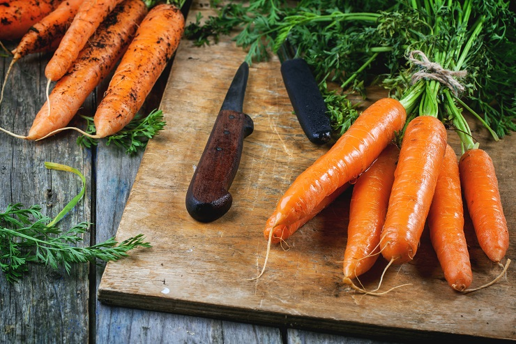 Bunch of fresh carrot with vintage knife on old cutting board.