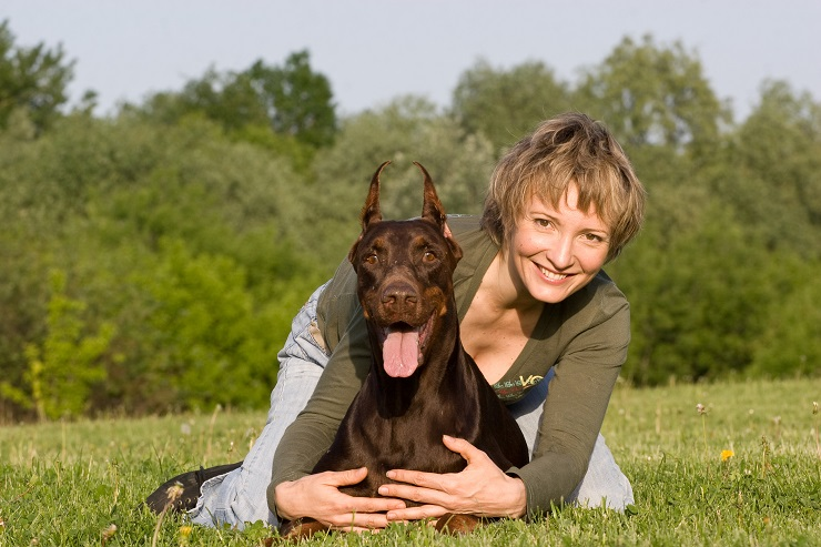 Mid adult woman lying on the grass in park embrasing the dobermann dog