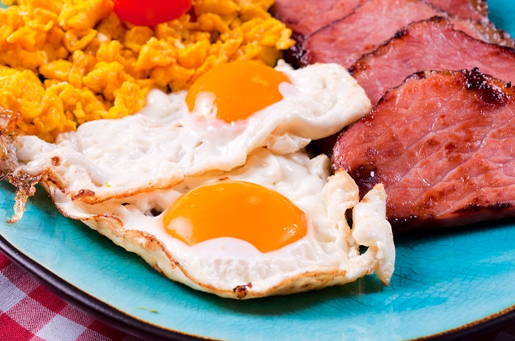 Strong breakfast with eggs and ham. Selective focus on the ham and eggs