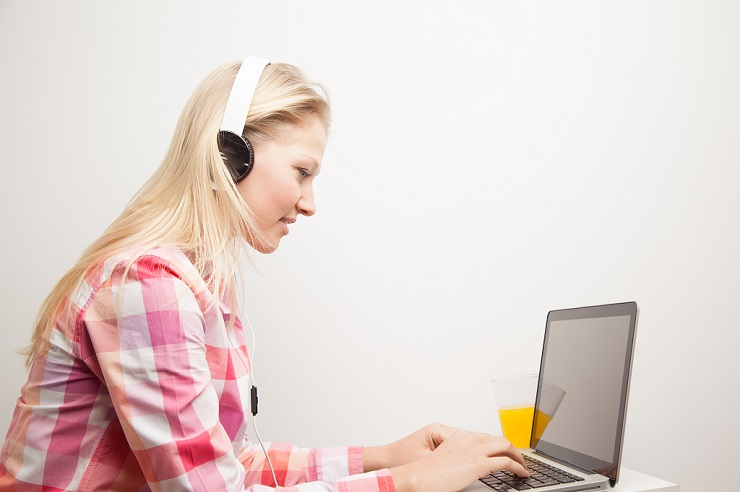 Woman listening to music and using the computer